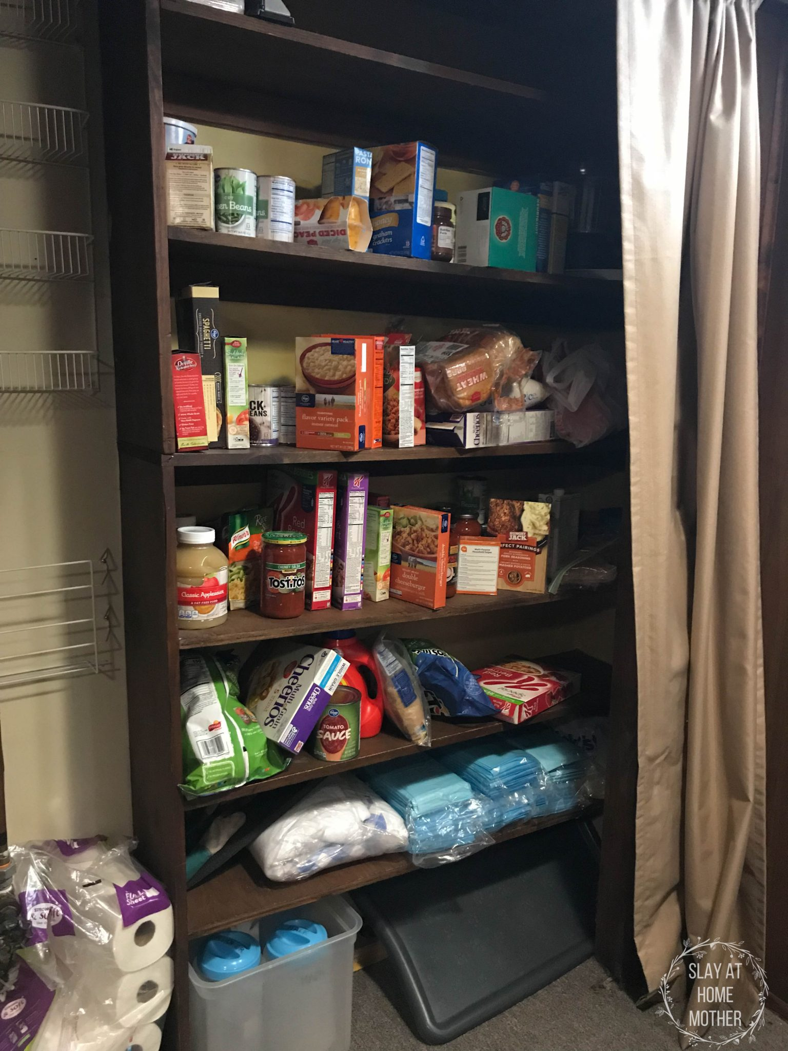 A side view of my messy pantry with brown shelves, tan curtains, and yellow walls