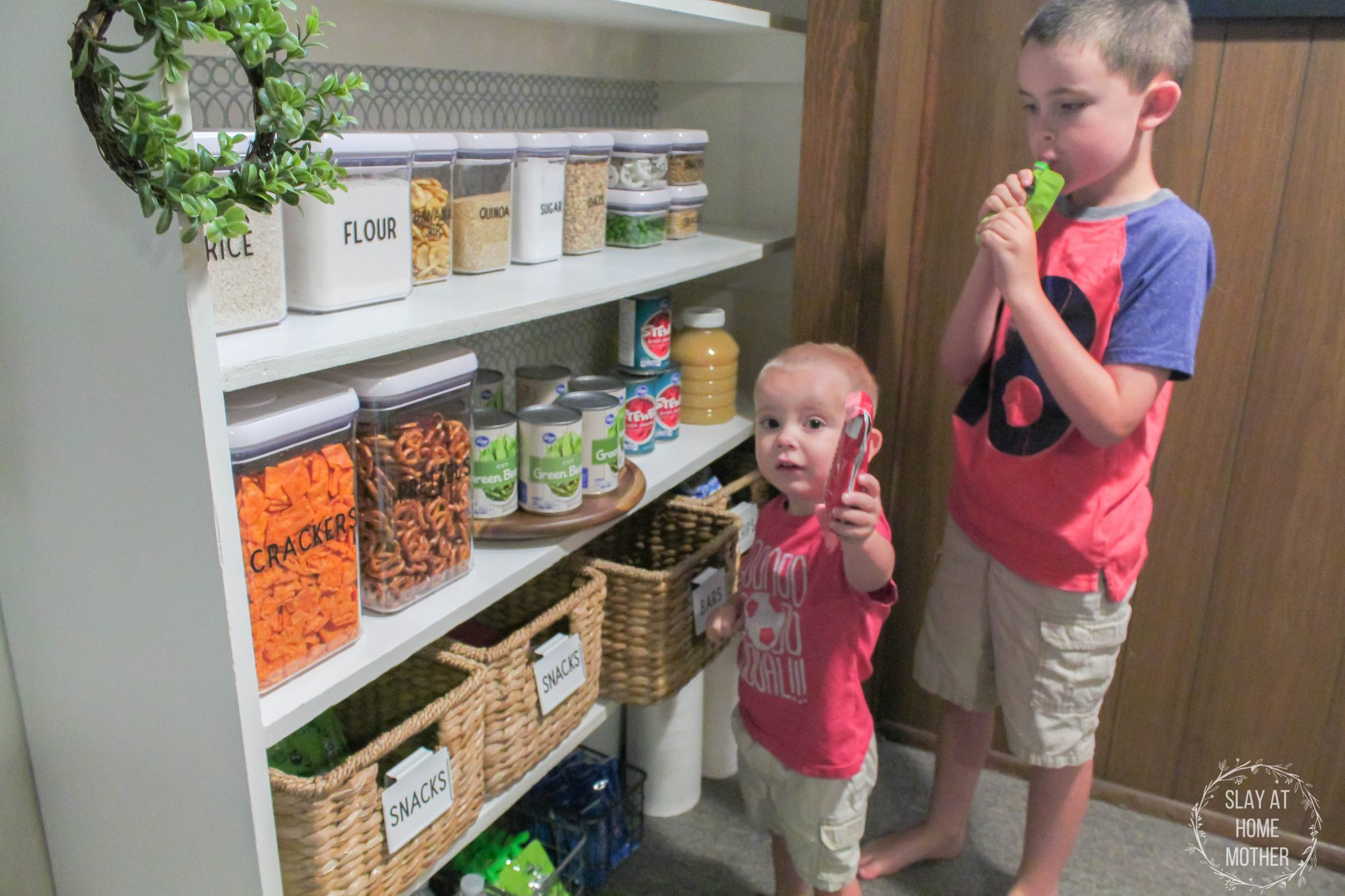 Our kids easily grabbing snacks from our snack shelf in our newly renovated pantry!