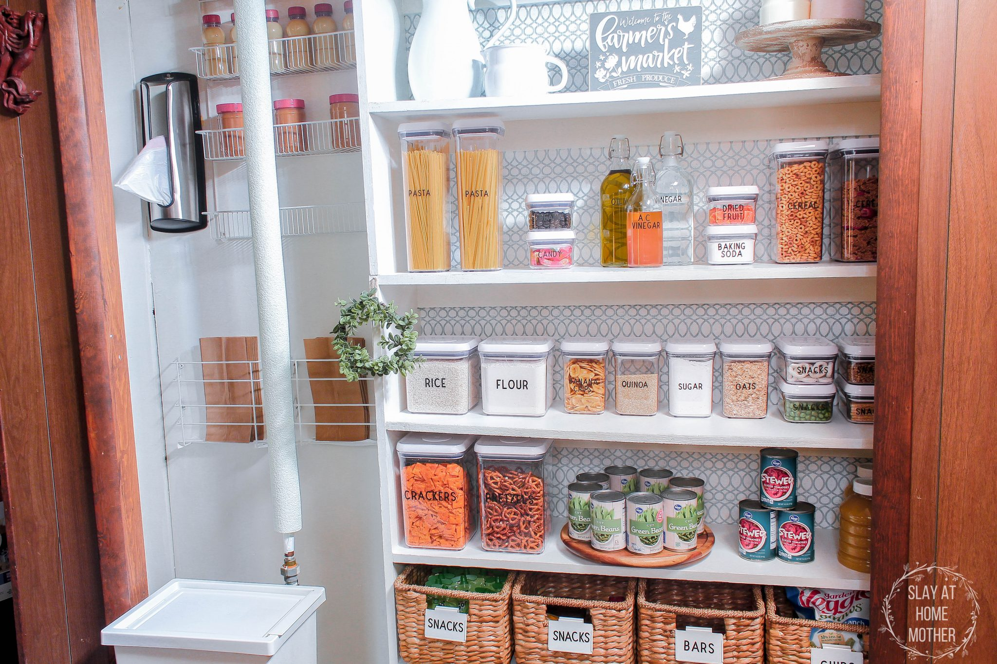My finished pantry with white walls, contact paper wallpaper, and dry goods organized in labeled bins and baskets