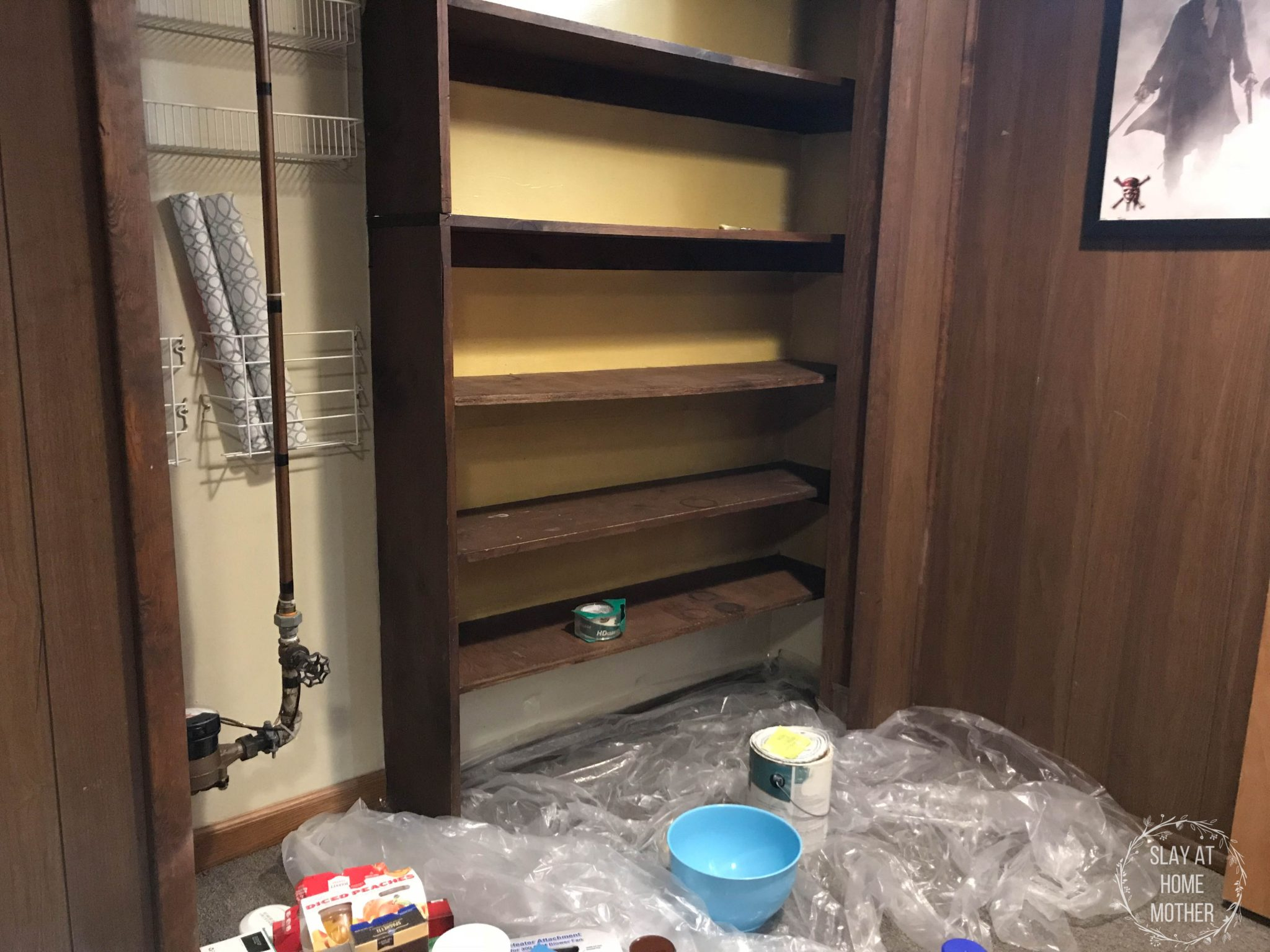 Cleared shelves in my pantry, plastic covering the carpeted basement floor