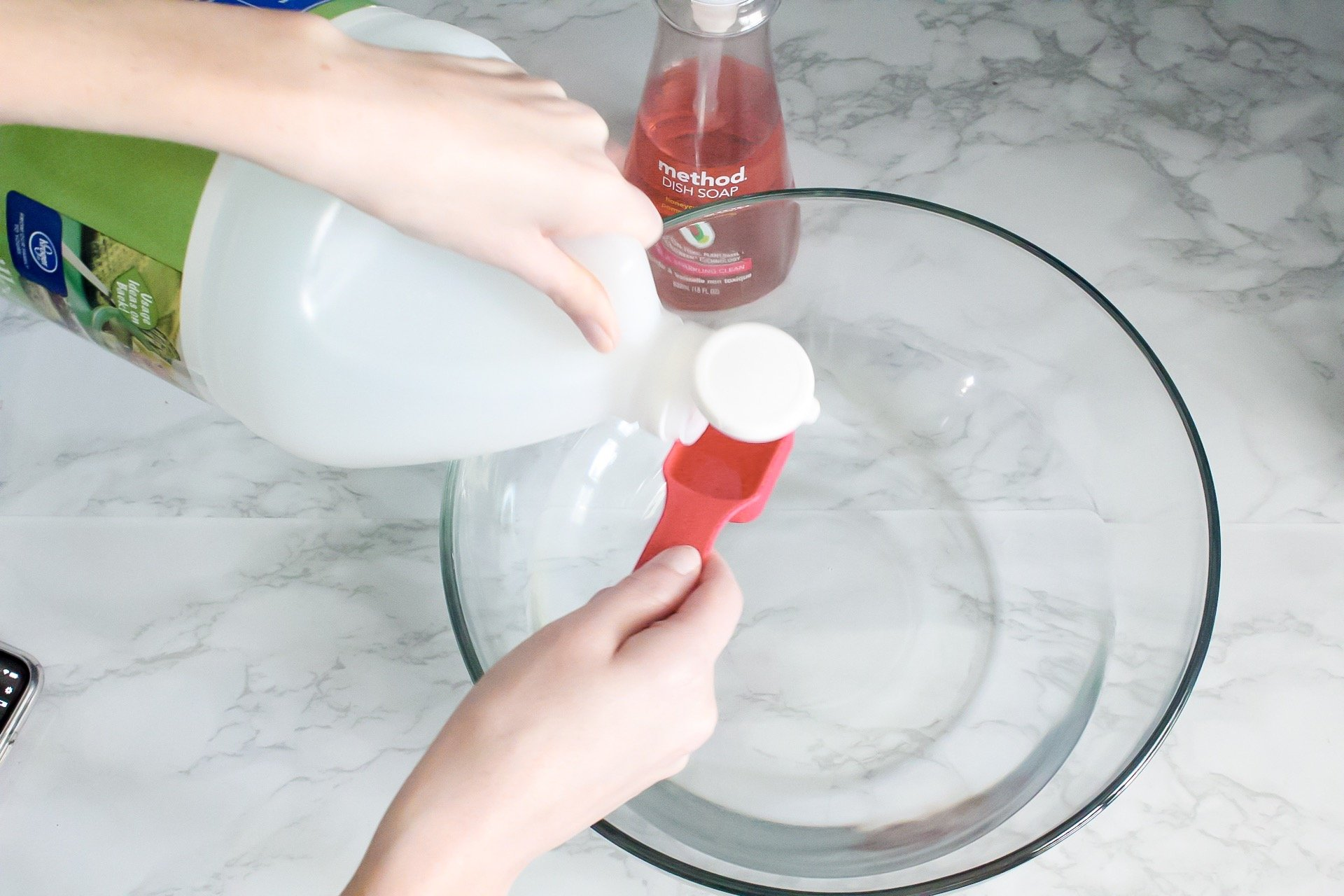 Measuring vinegar into tablespoon to put into homemade cleaning solution