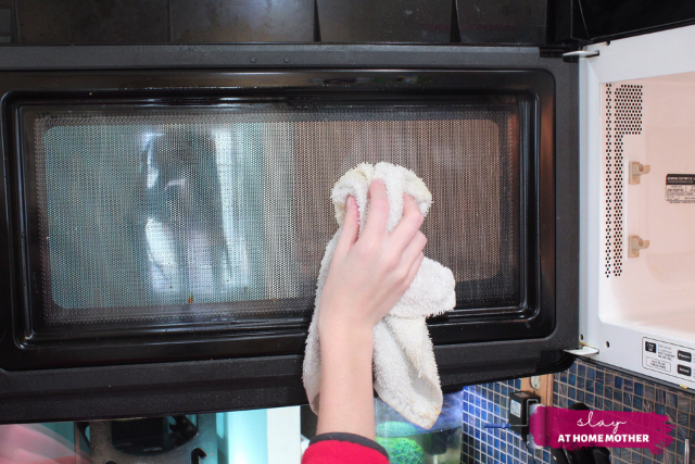 wiping down the inside of the microwave door with a wet wash rag