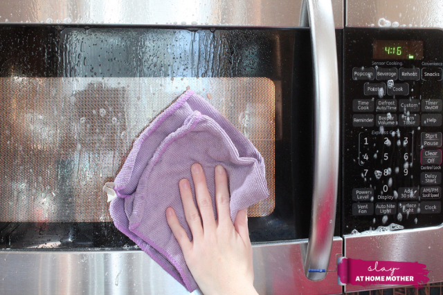 wiping down the outside of the microwave with microfiber cloth