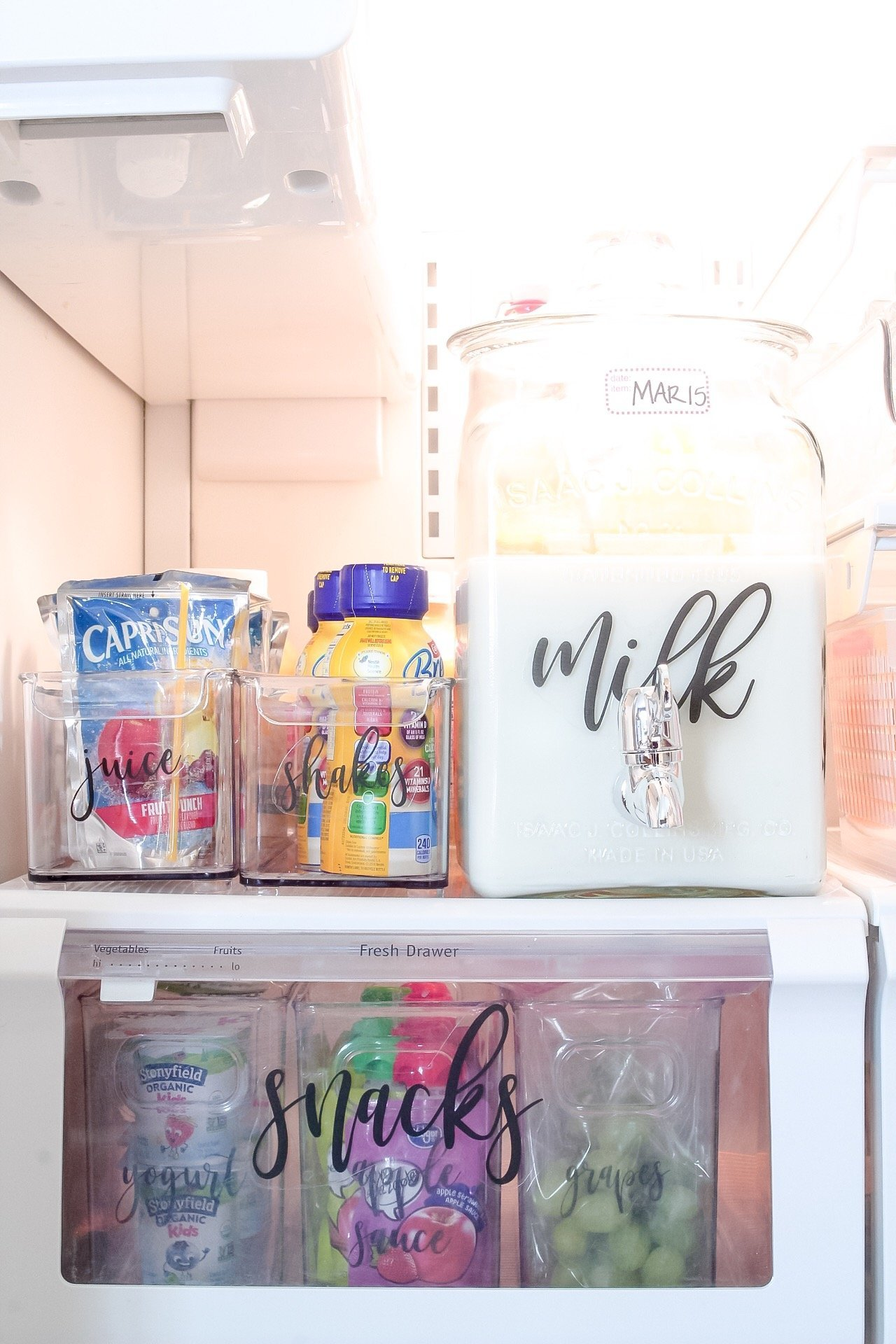 A closeup of our drinks in our fridge - including our milk in a beverage dispenser, and our kids' shakes and juices in long containers