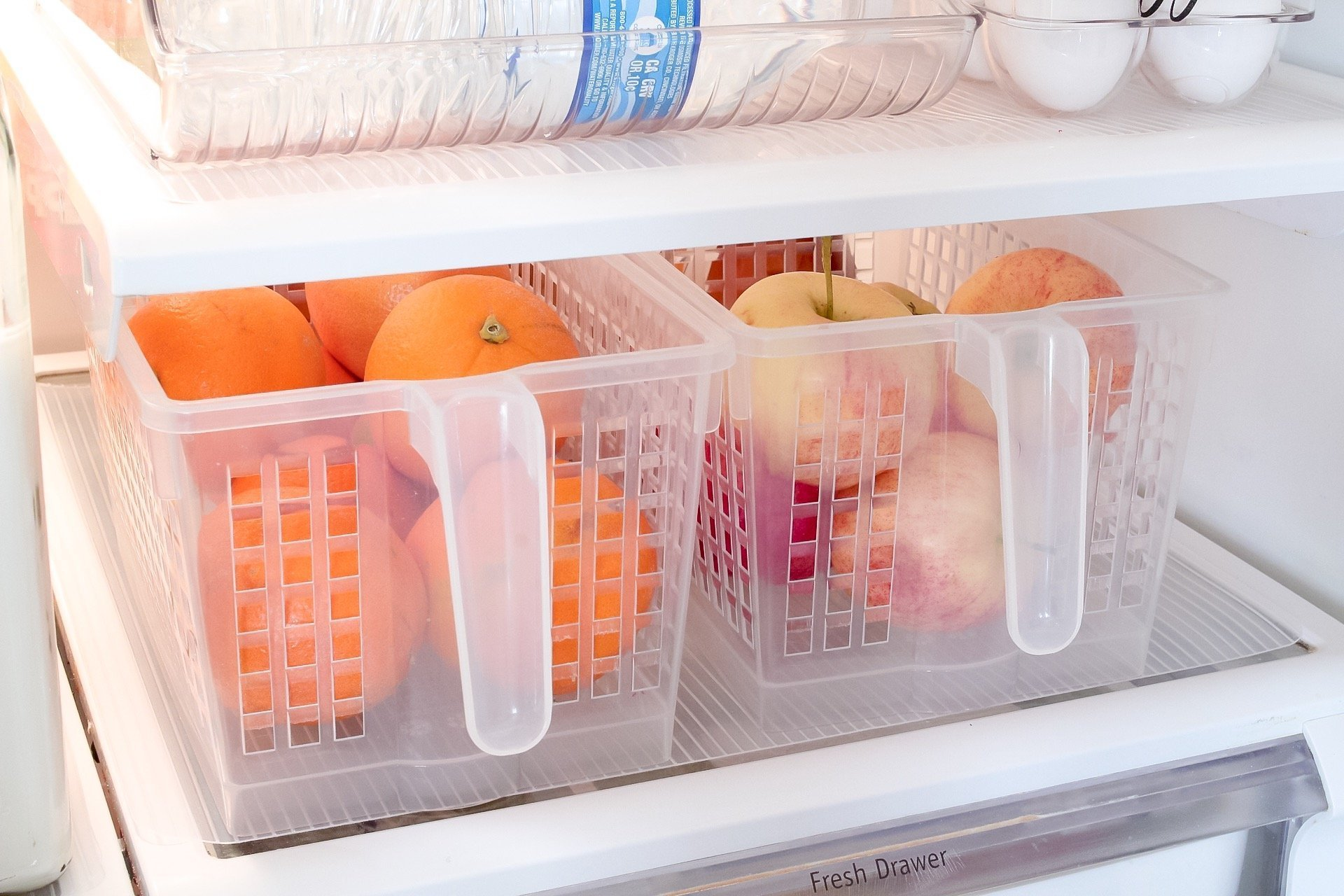 Apples and oranges in small storage baskets inside our fridge with handles for easy pull-out and grab