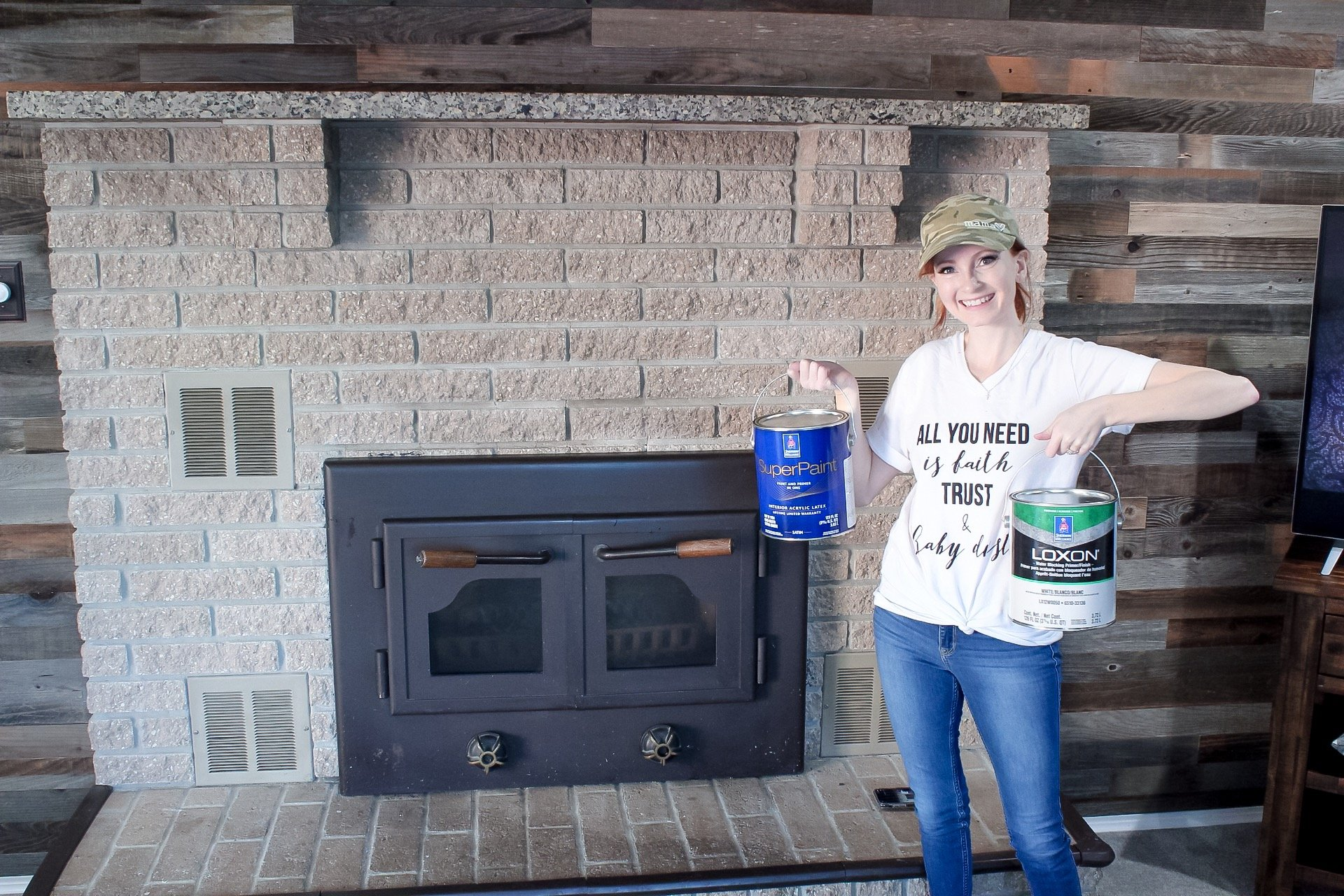 Corinne of Slayathomemother.com holding up paint cans in front of my tan fireplace, ready to paint!