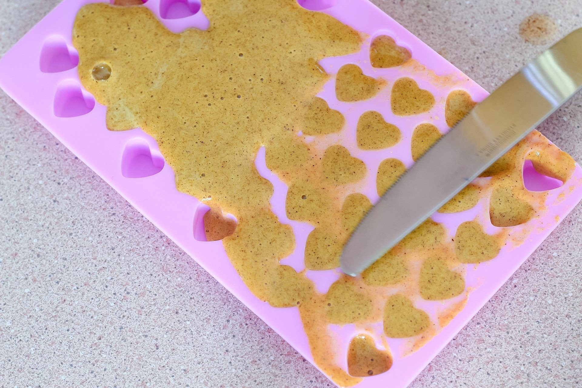 Smoothing homemade gummy mixture into silicone molds