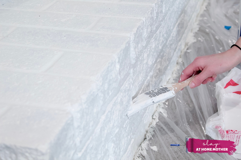 Painting grout lines of brick fireplace with SuperPaint and 2-inch paintbrush in color Extra White