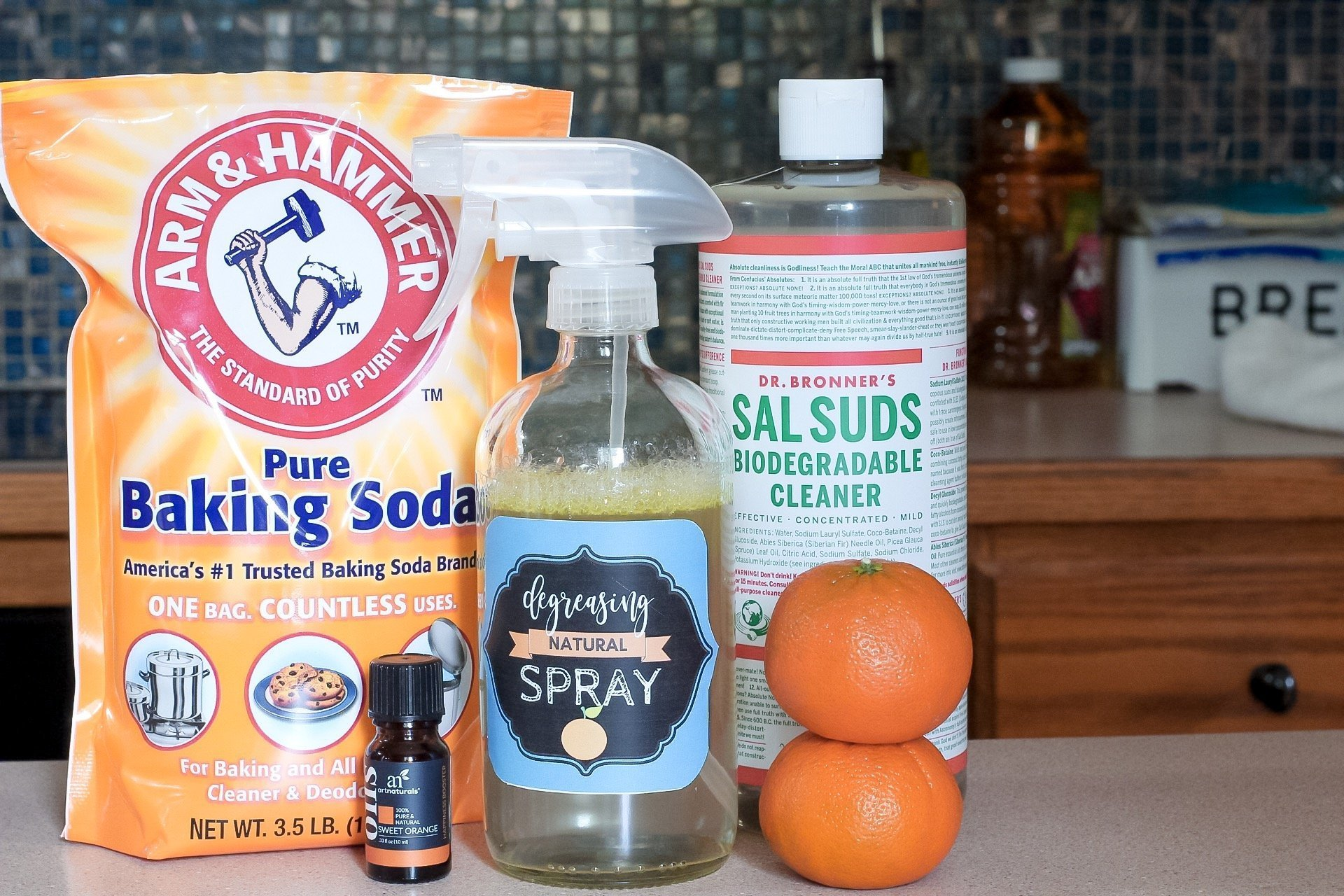Kitchen And Stove Degreaser Ingredients: Baking soda, Sal's Suds, sweet orange essnetial oil, and glass bottle of kitchen greaser