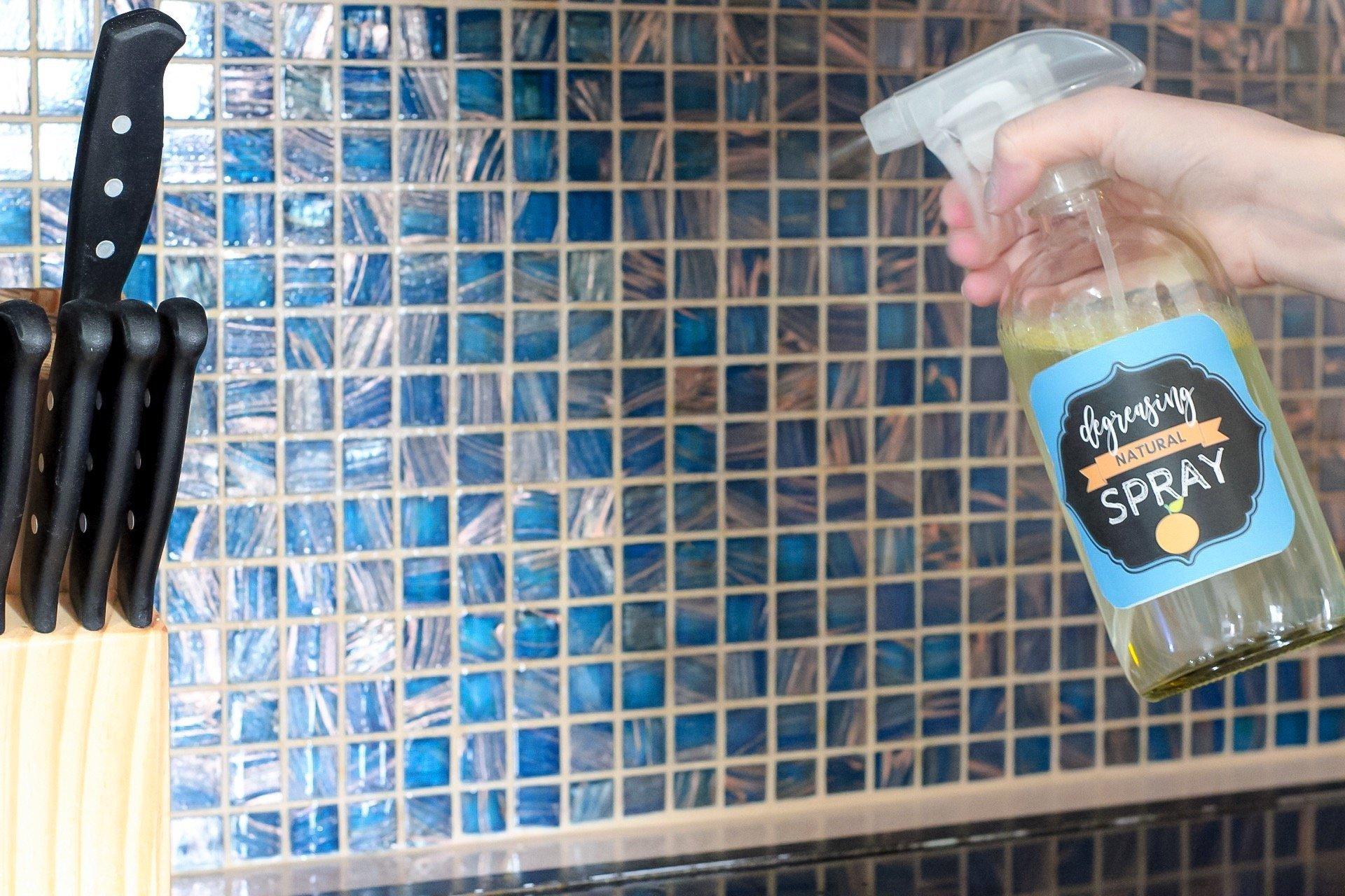 Spraying homemade kitchen degreaser onto kitchen backsplash