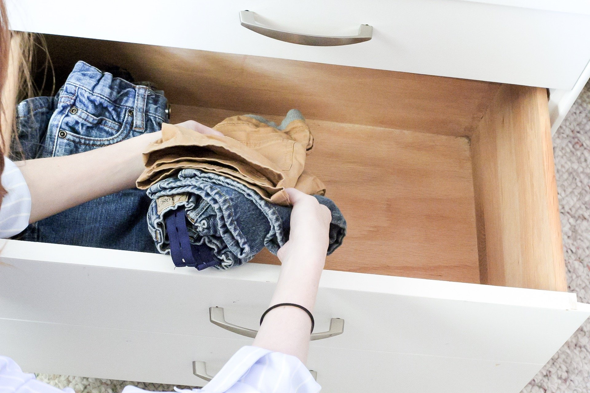 Putting freshly cleaned and folded clothes into drawers