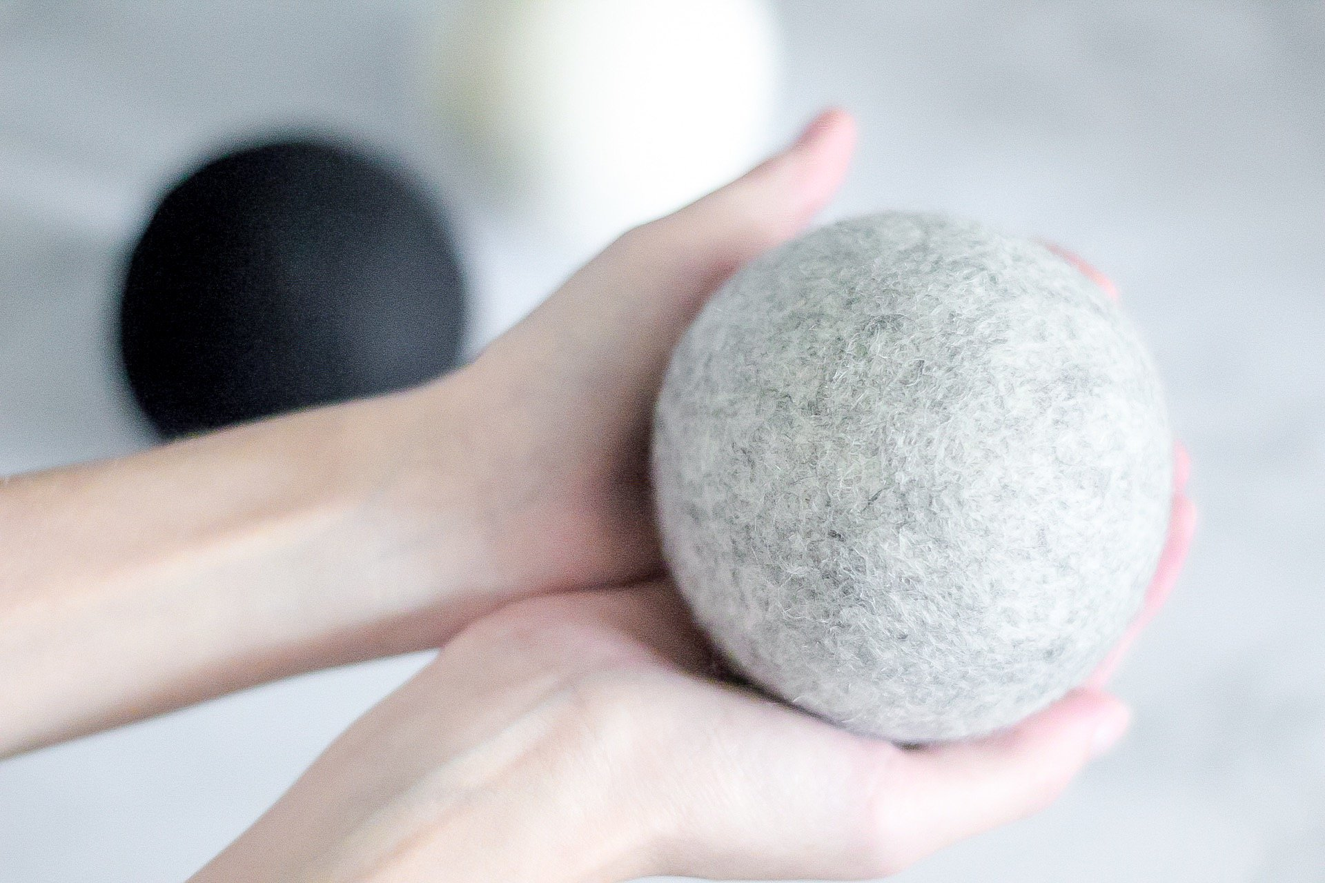 holding dropps wool dryer ball in gray