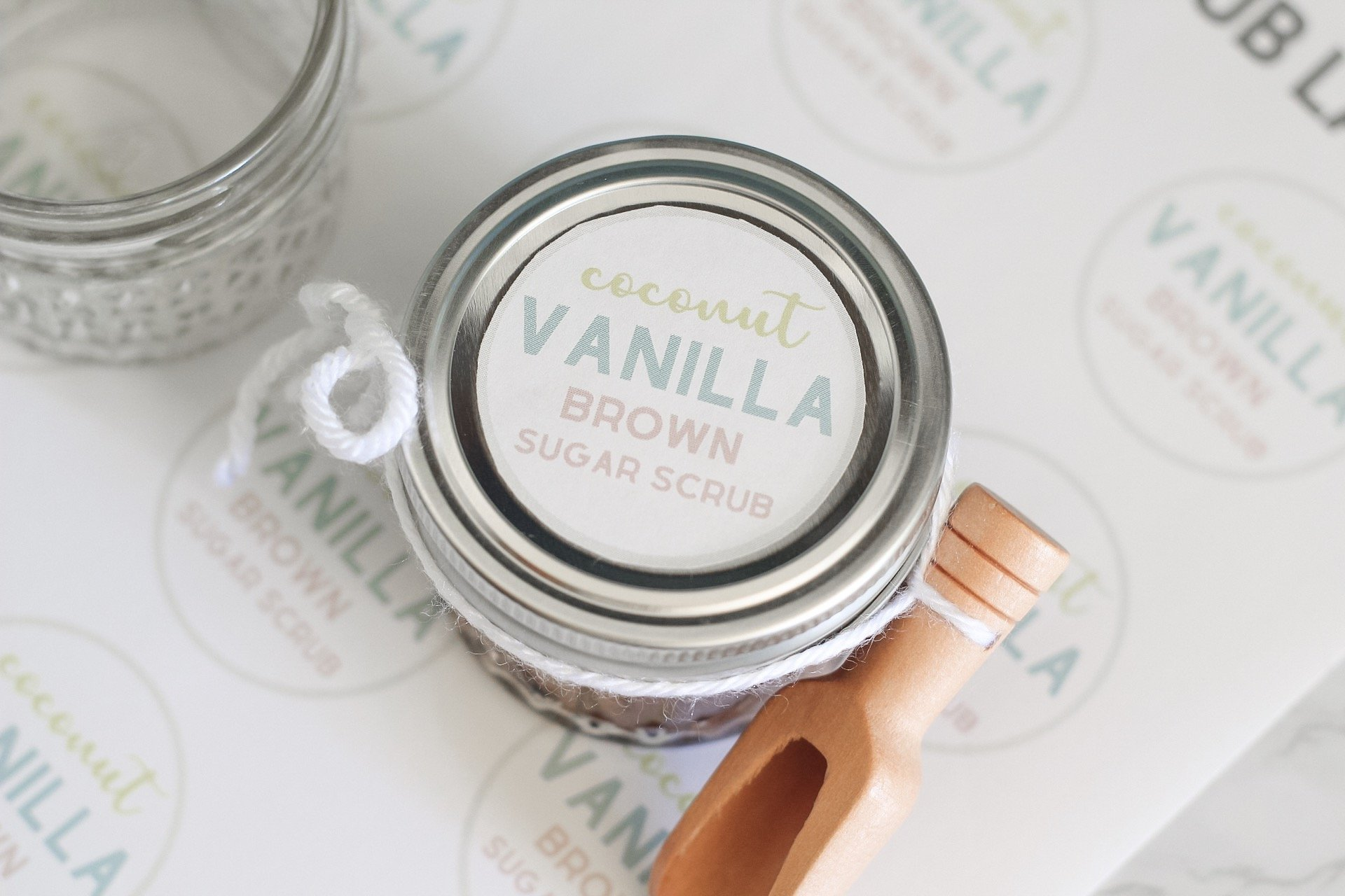 homemade sugar scrub with scoop on top of labels