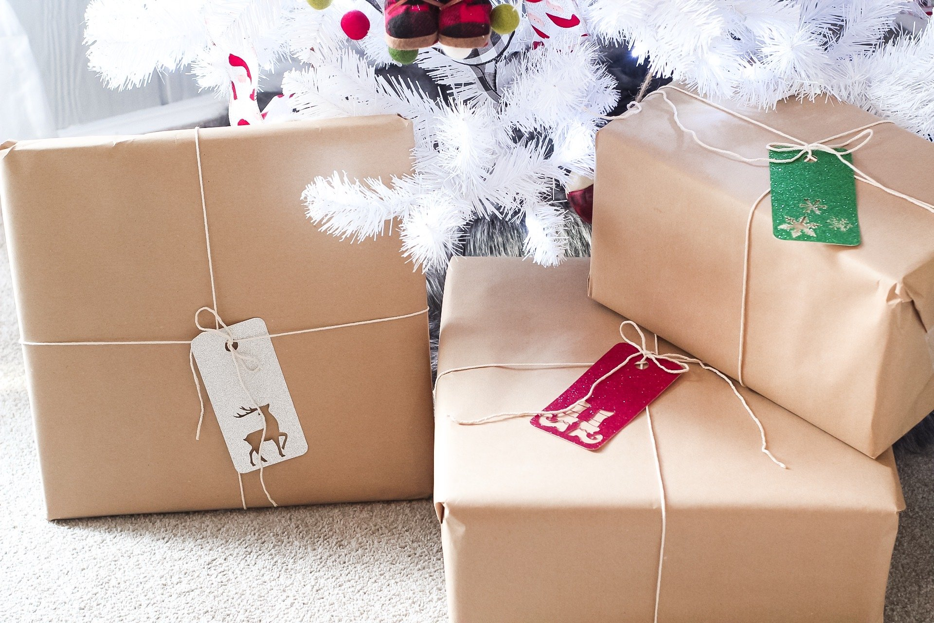 Christmas presents wrapped with brown wrapping paper and string with glitter gift tags attached