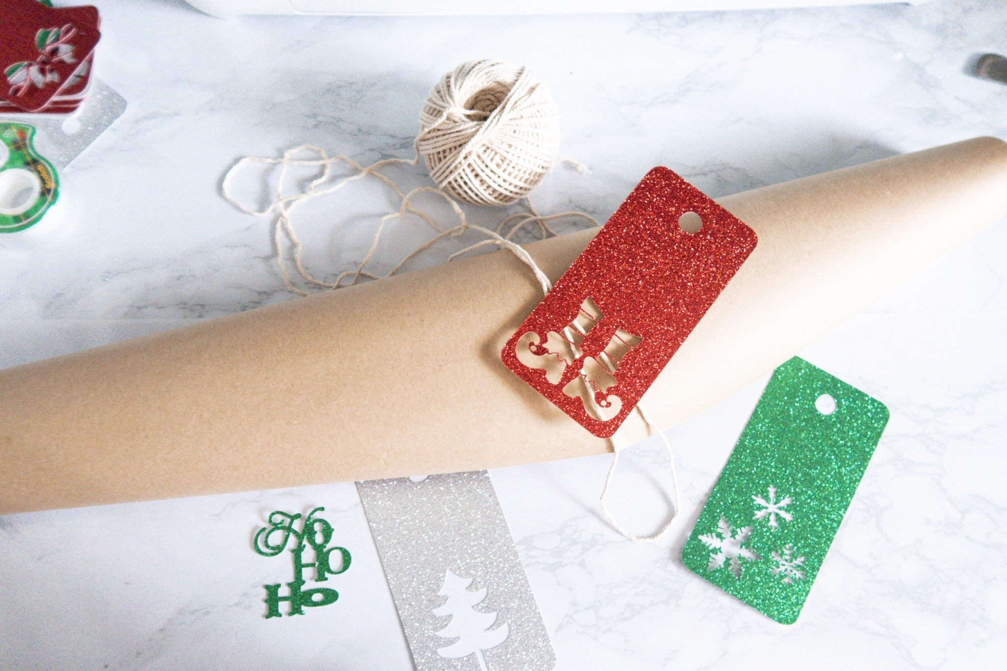 flatlay of christmas gift tags wrapping paper and string