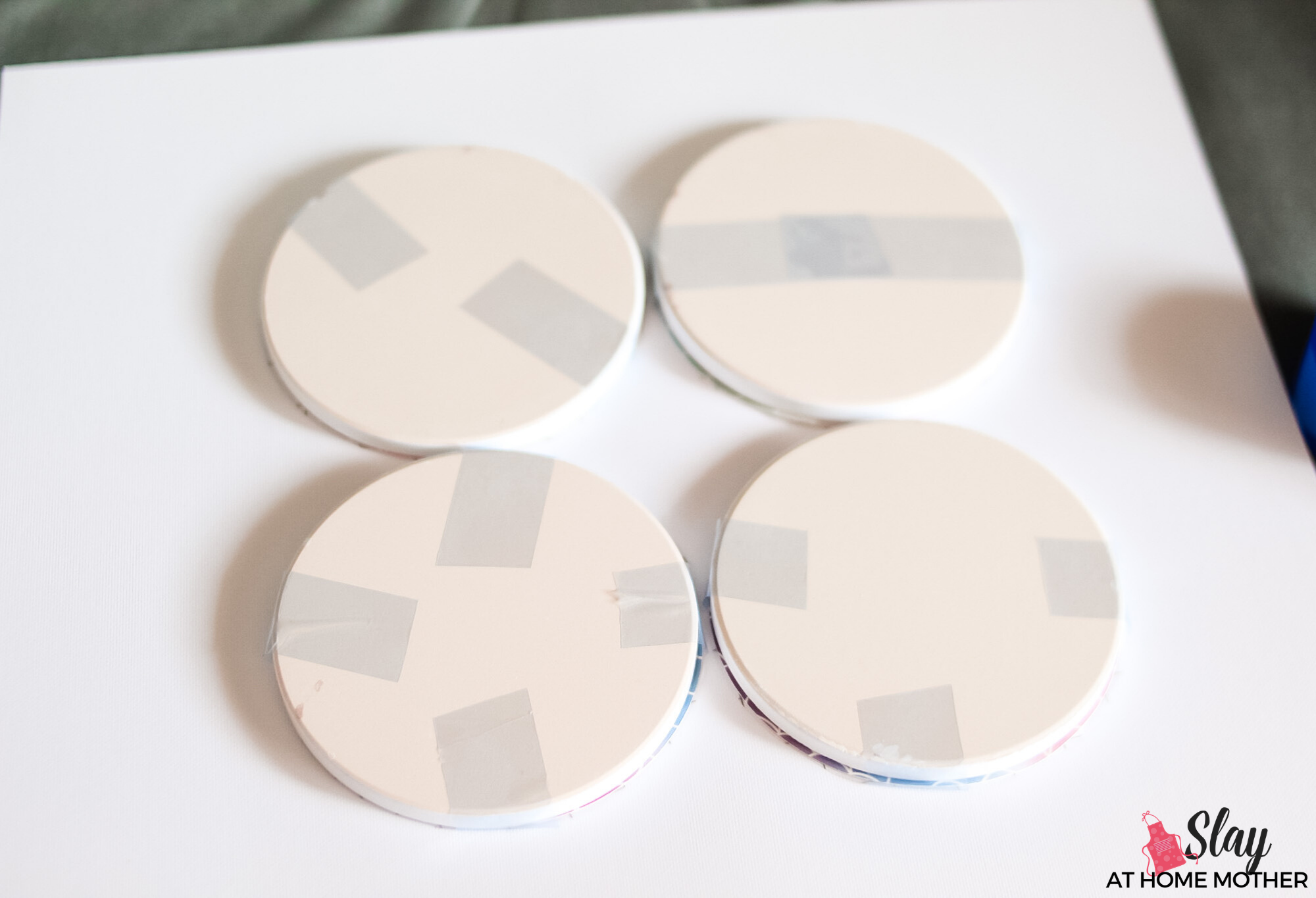 cricut coasters with infusible ink taped on face down on cardstock