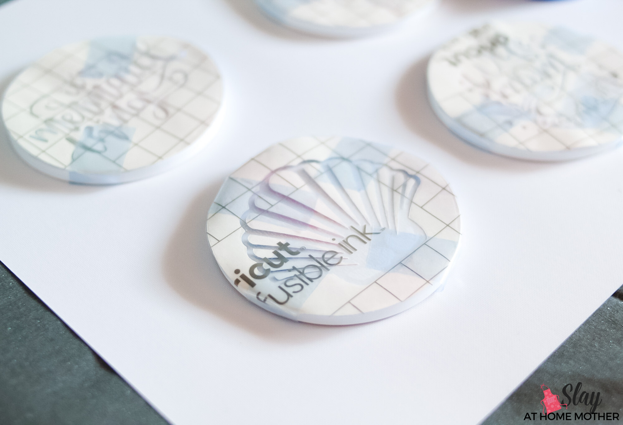 infusible ink transfer sheets taped onto coasters with heat resistant tape